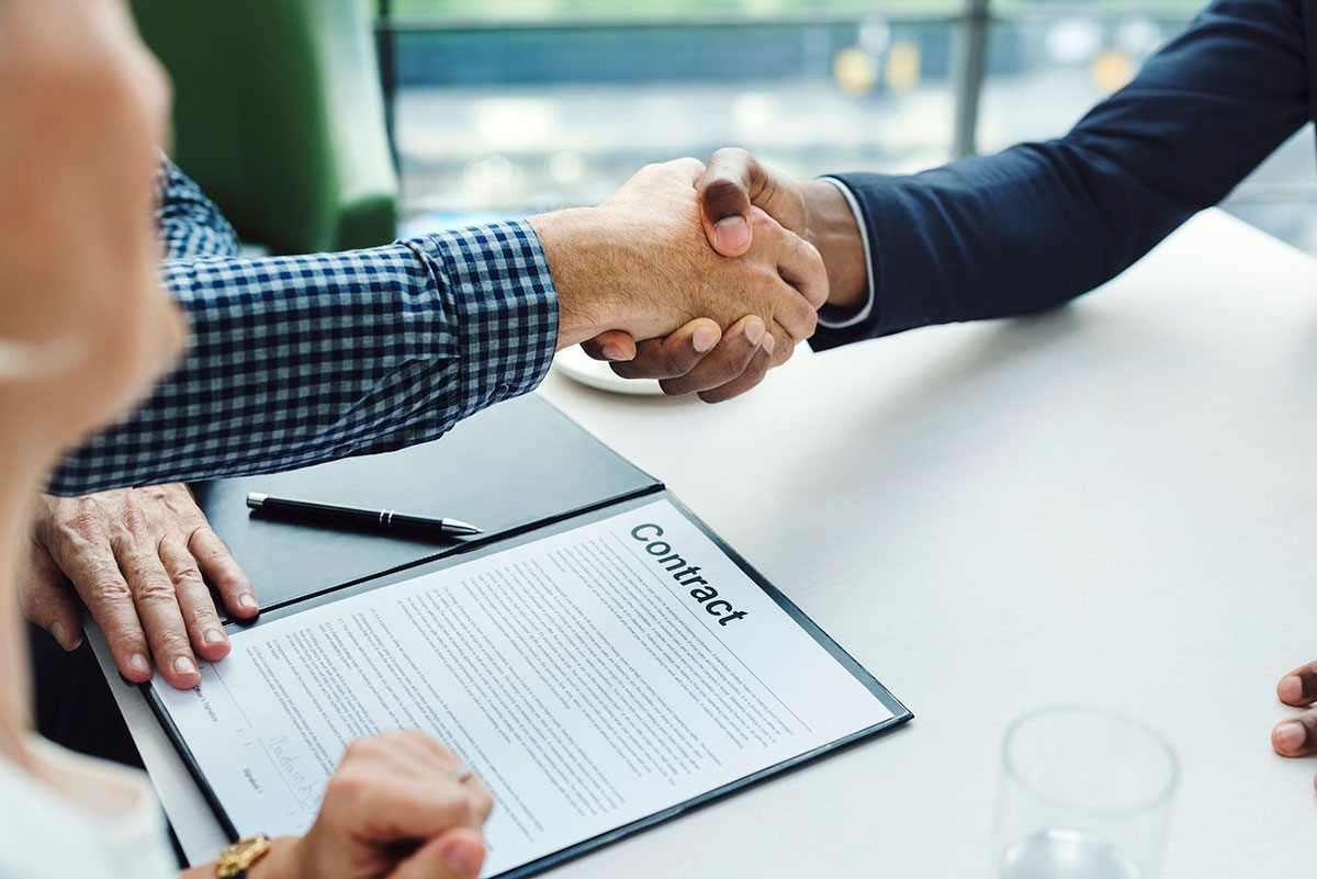 Two men shaking hands over contract
