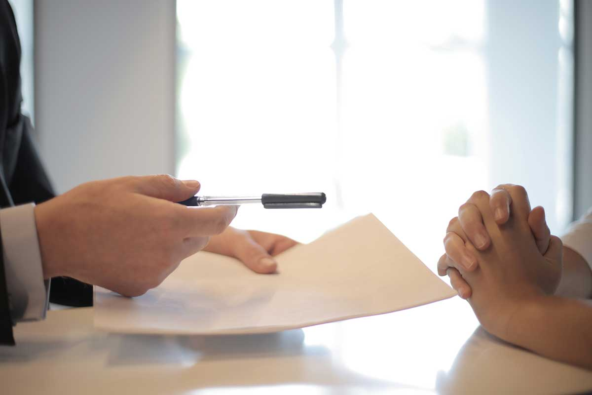 Business professional handing a pen and contract to an individual